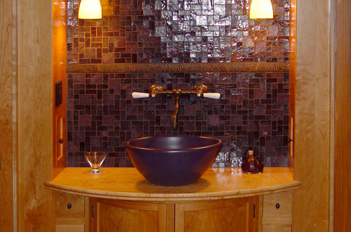 Basin with curved cabinetry and tile backsplash