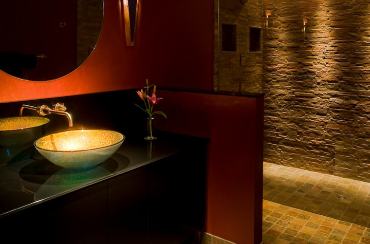 Dramatic Bathroom Featuring Theatrically Lit Stone, Granite, Tile, and Glass