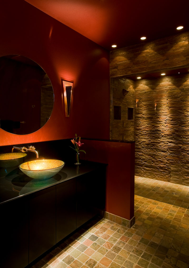 Stone tile walls, glass shower wall, granite countertop, arty basin, serene lighting