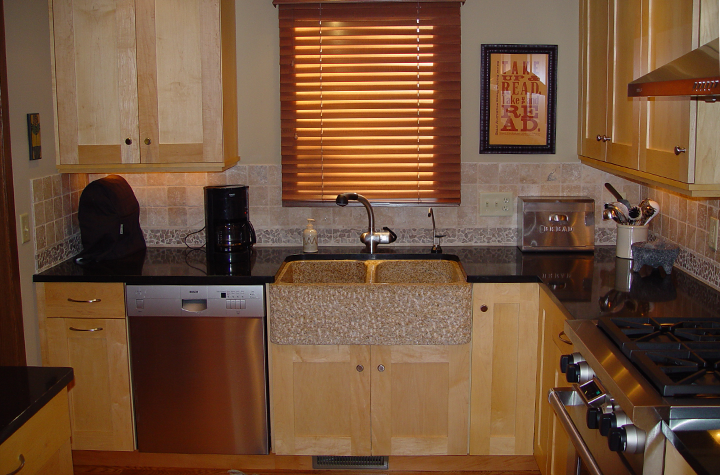 Speckled granite farmhouse-style sink, textured tile backsplash, classic fixtures, maple cabinetry