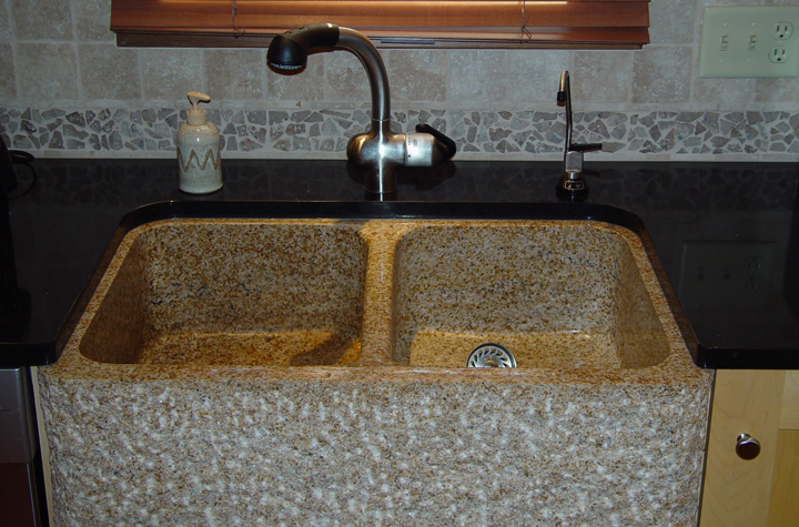 Detail: Speckled granite farmhouse-style sink, textured tile backsplash, classic fixtures