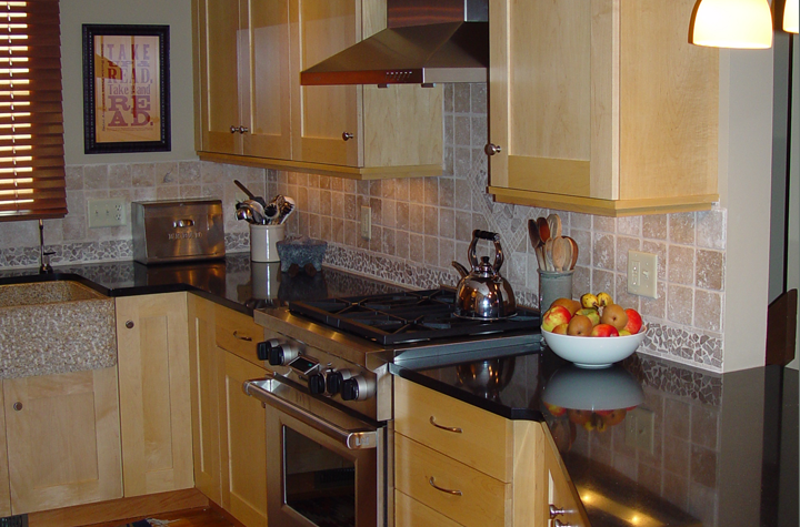Gas range, marble counter, tile backsplash, maple cabinetry