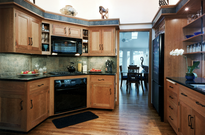 Corner appliances with granite counter and tile backsplash, custom woodwork, shelving above